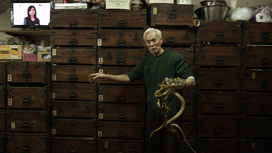 Dono de uma loja de sopas de cobra exibe suas iguarias na China continental.